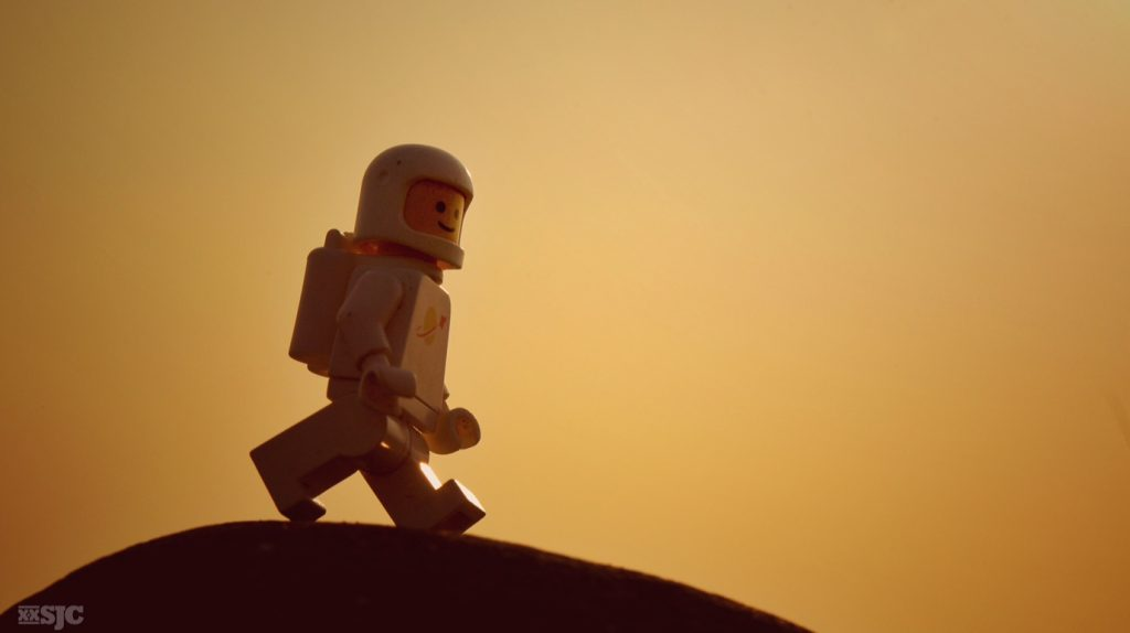 white classic lego spaceman walks across a rock in the golden glow of a setting sun.